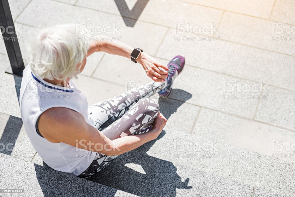 Senior lady having rest time on granitical stairs outdoor stock photo