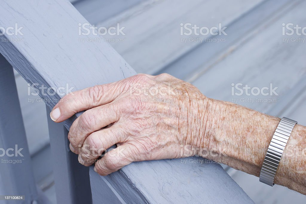Senior lady holding stair rail stock photo