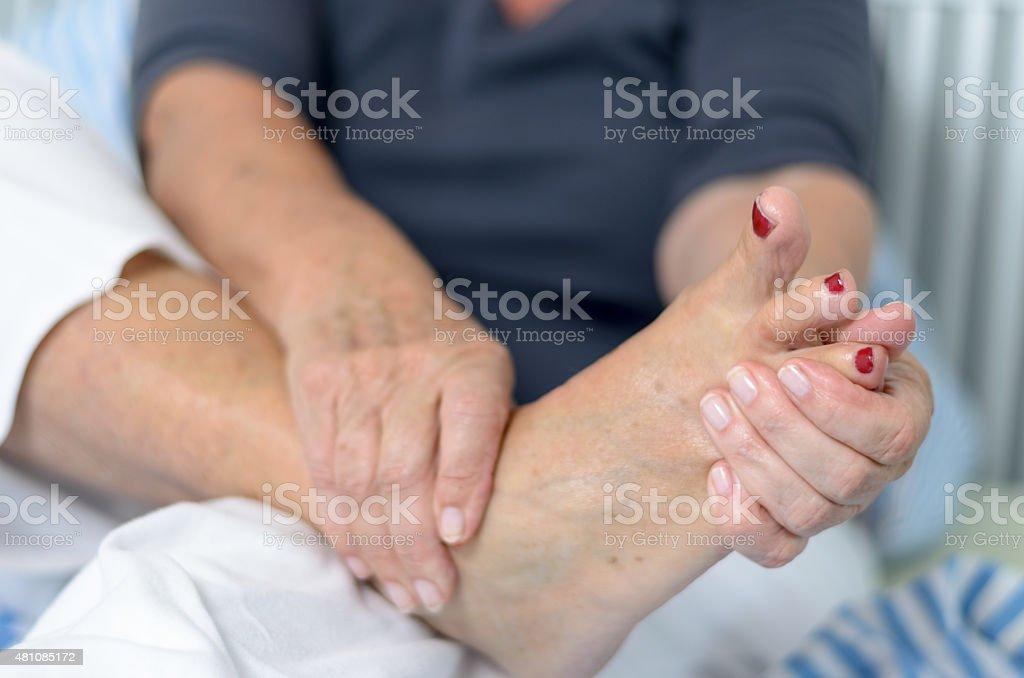 Senior lady massaging her foot stock photo