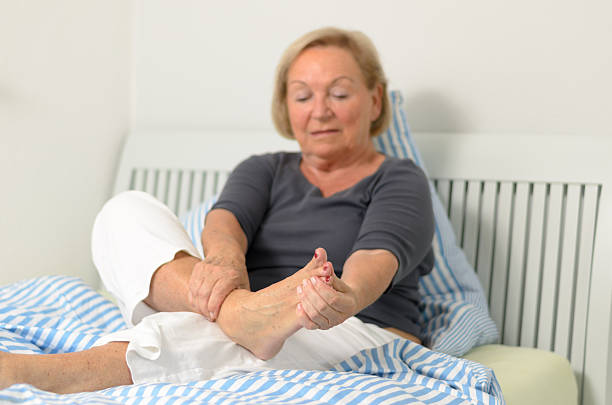 Senior lady massaging her foot Senior lady massaging her bare foot to relive aches and pains as she sits relaxing against the pillows on her bed sole of foot stock pictures, royalty-free photos & images