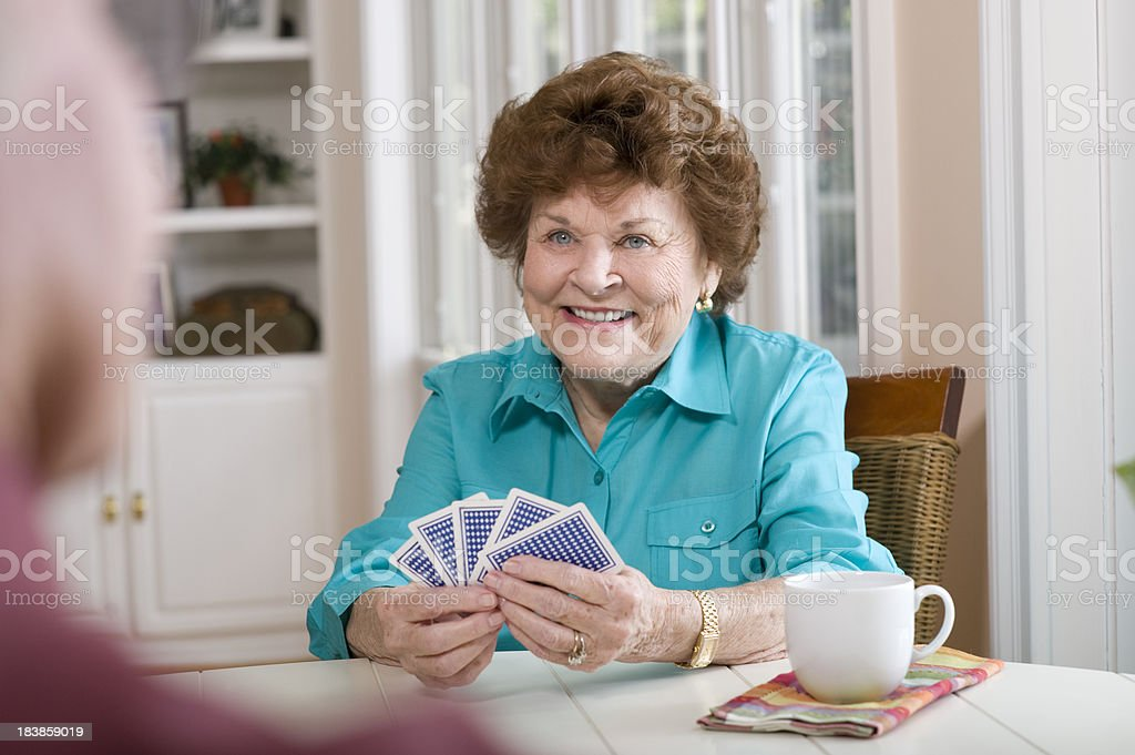 Senior lady playing a card game royalty-free stock photo