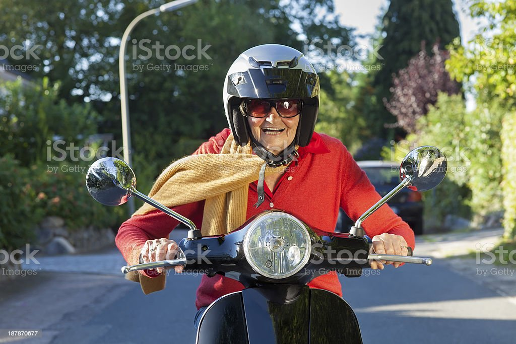 Senior lady riding her scooter. stock photo