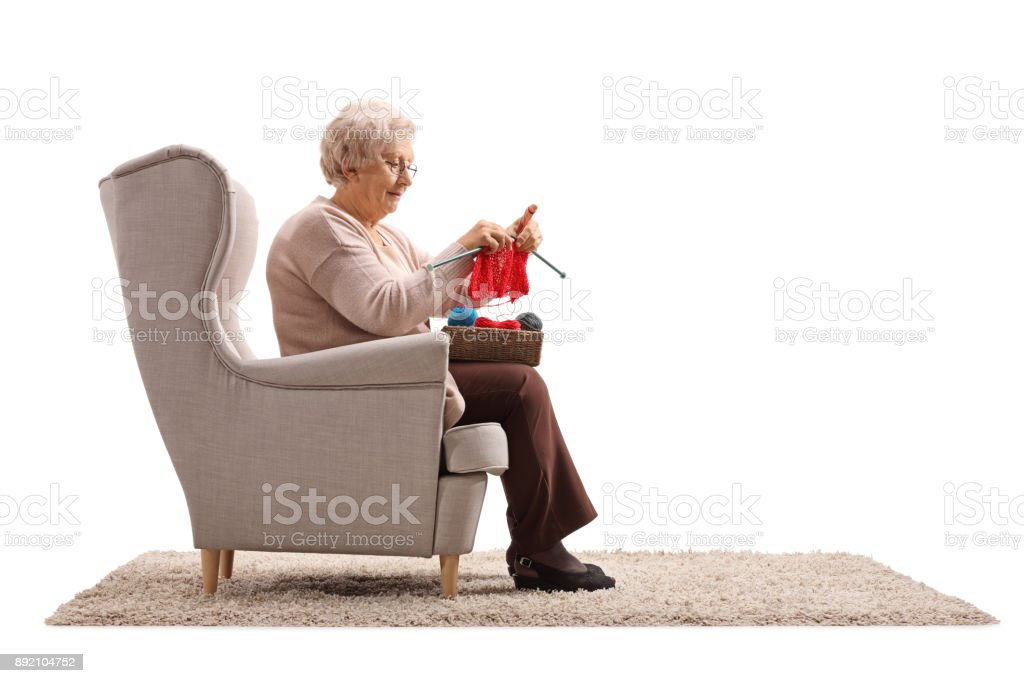 Senior lady sitting in an armchair and knitting stock photo
