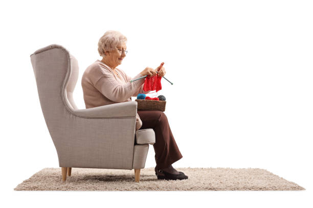 Senior lady sitting in an armchair and knitting - foto stock