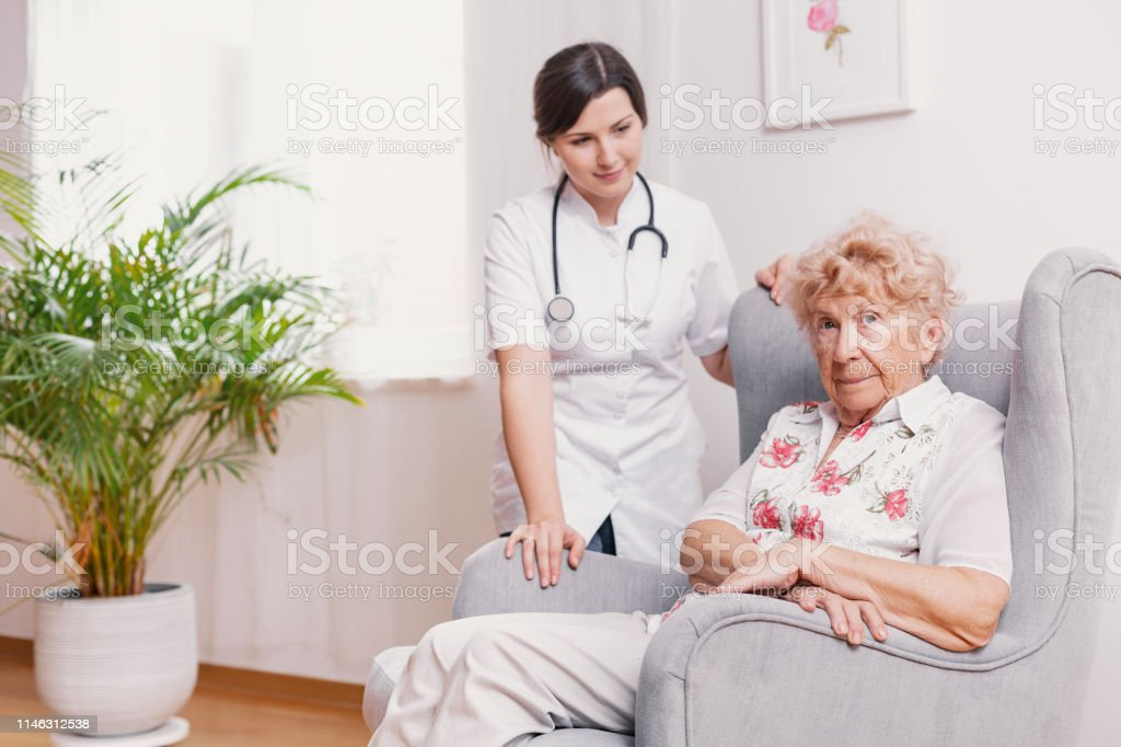Senior lady sitting in armchair at nursing home, supporting nurse...