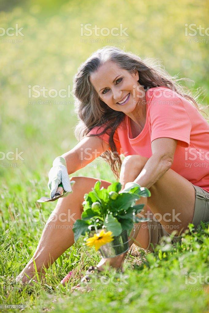 Senior Lady Sitting In Flowers royalty-free stock photo