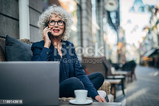 One woman, modern mature lady with gray hair, talking on mobile phone in sidewalk cafe.