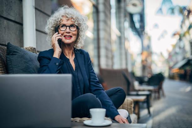 dame aînée parlant sur l'extérieur mobile dans le café - une seule femme senior photos et images de collection