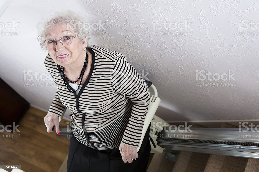 Senior Lady Uses A Stair Lift To Help Her Disability royalty-free stock photo