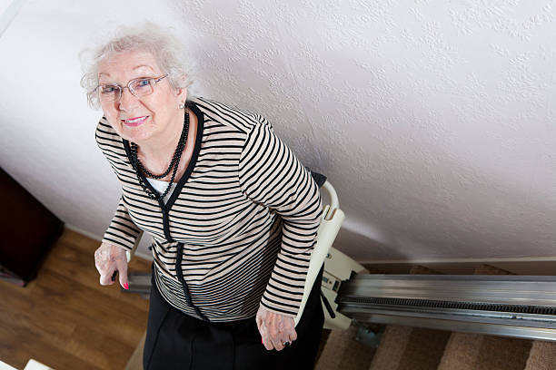 Senior Lady Uses A Stair Lift To Help Her Disability stock photo