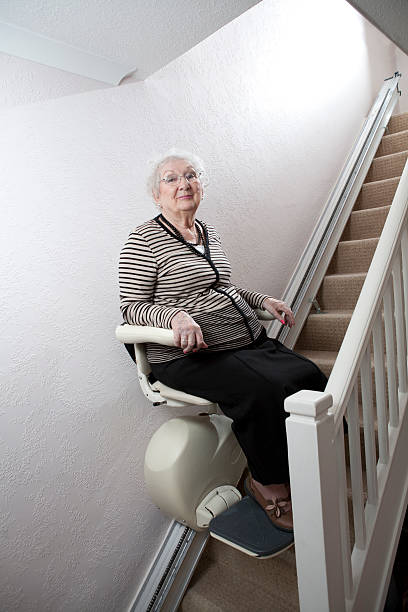 Senior lady who has mobility issues uses a Stair Lift stock photo