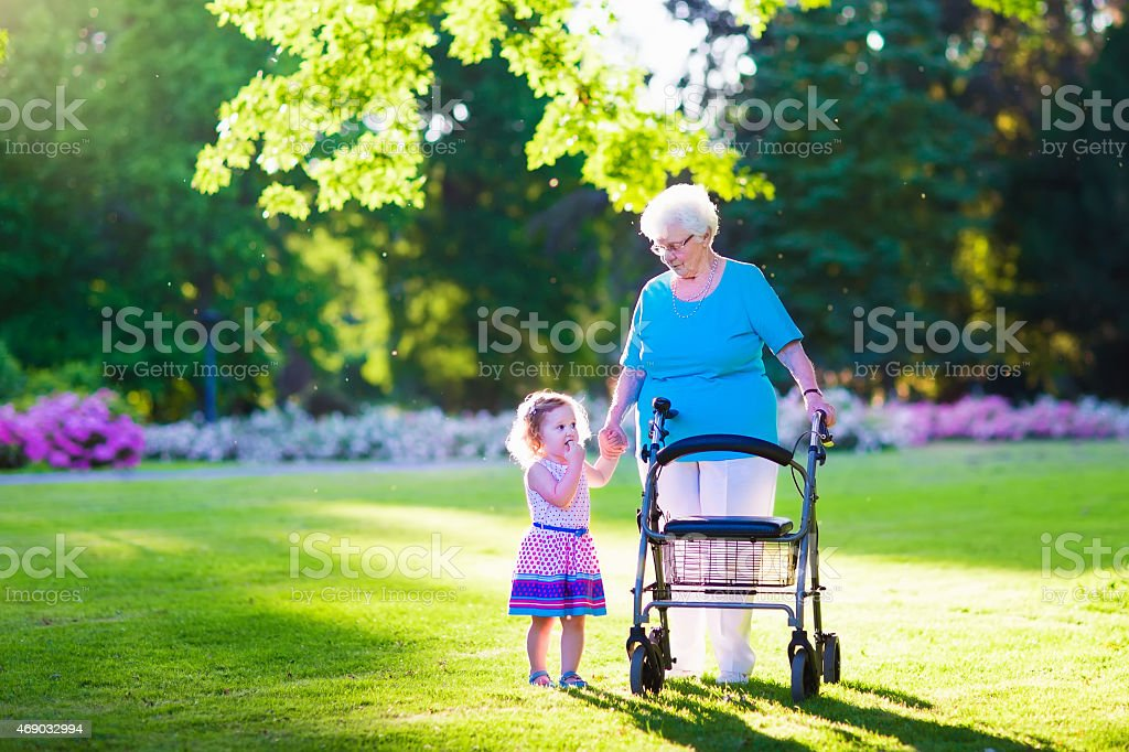 Senior lady with a walker and little girl in park stock photo