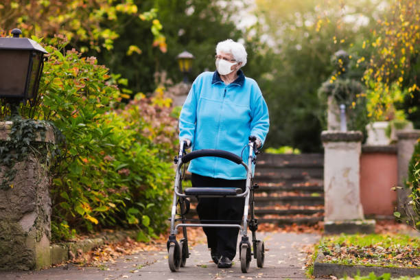 Senior lady with a walker in face mask stock photo
