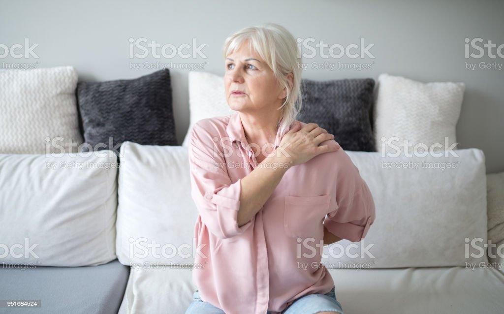 Senior dame avec des douleurs dorsales, assis sur le canapé photo libre de droits