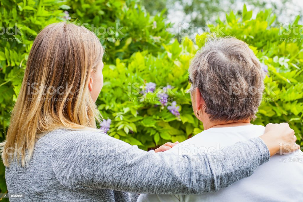 Senior lady with caregiver back view stock photo