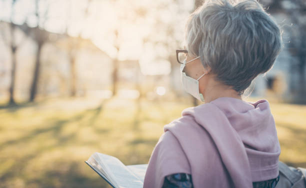 Senior lady with face mask reading the bible in front of a church stock photo