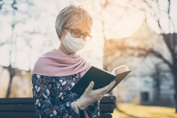 Seniorin mit Gesichtsmaske liest die Bibel vor einer Kirche – Foto