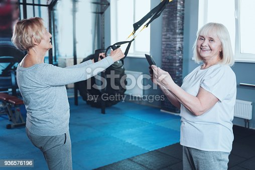 936573360 istock photo Senior lady with tablet computer smiling near friend stretching behind 936576196