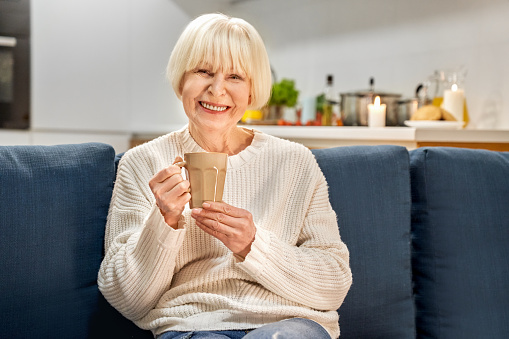 Senior lady woman at sofa holding cup of tea. Peaceful joy active confident beauty female drink. Positive old person relaxing dream think look camera at home. Cozy house interior concept, horizontal
