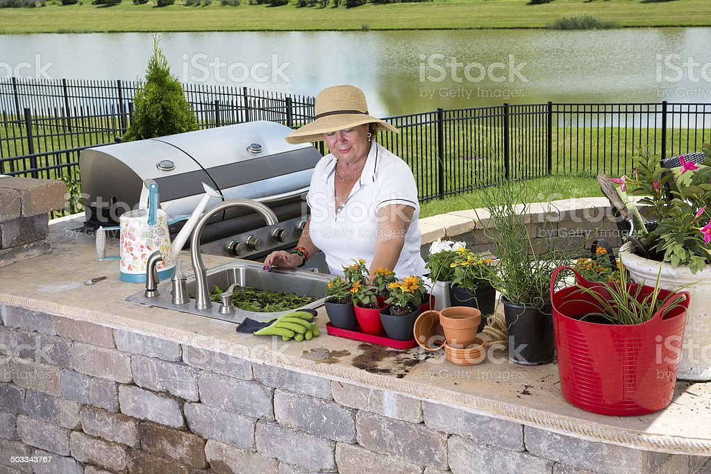Senior lady working in her summer kitchen stock photo