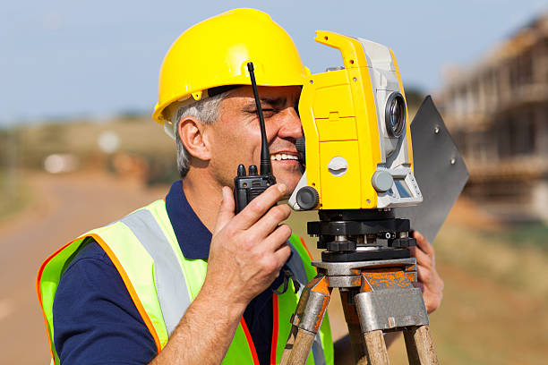 senior land surveyor working with tacheometer stock photo