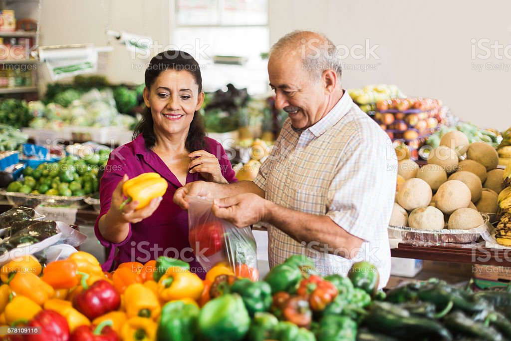 Senior latin couple buying bell peppers at supermarket stock photo