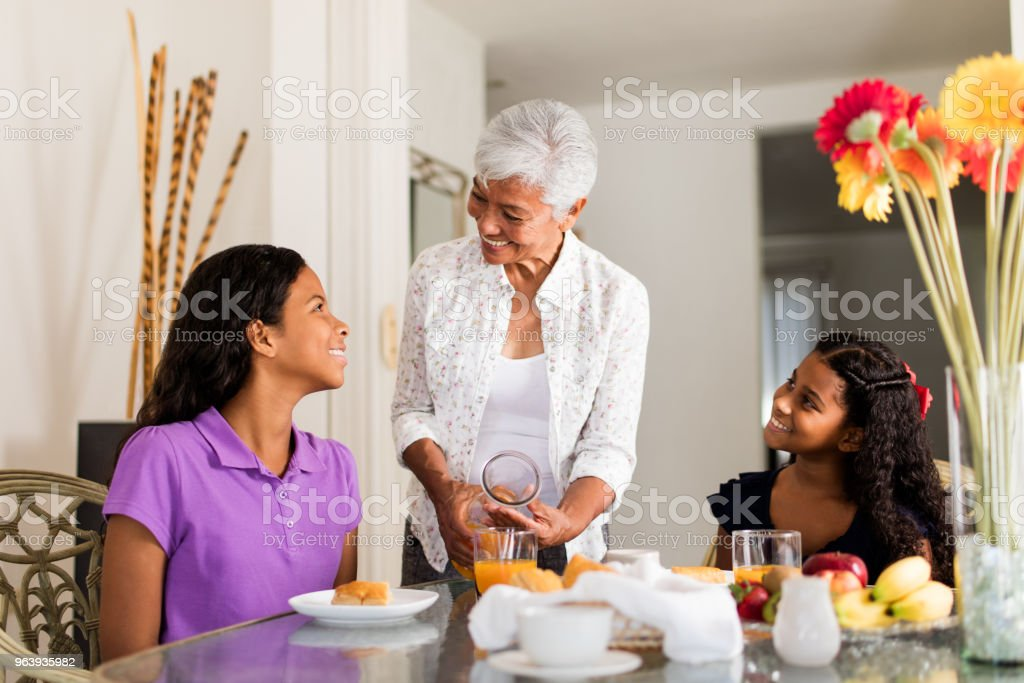 Senior latin woman serving food to her granddaughters - Royalty-free 12-13 Years Stock Photo