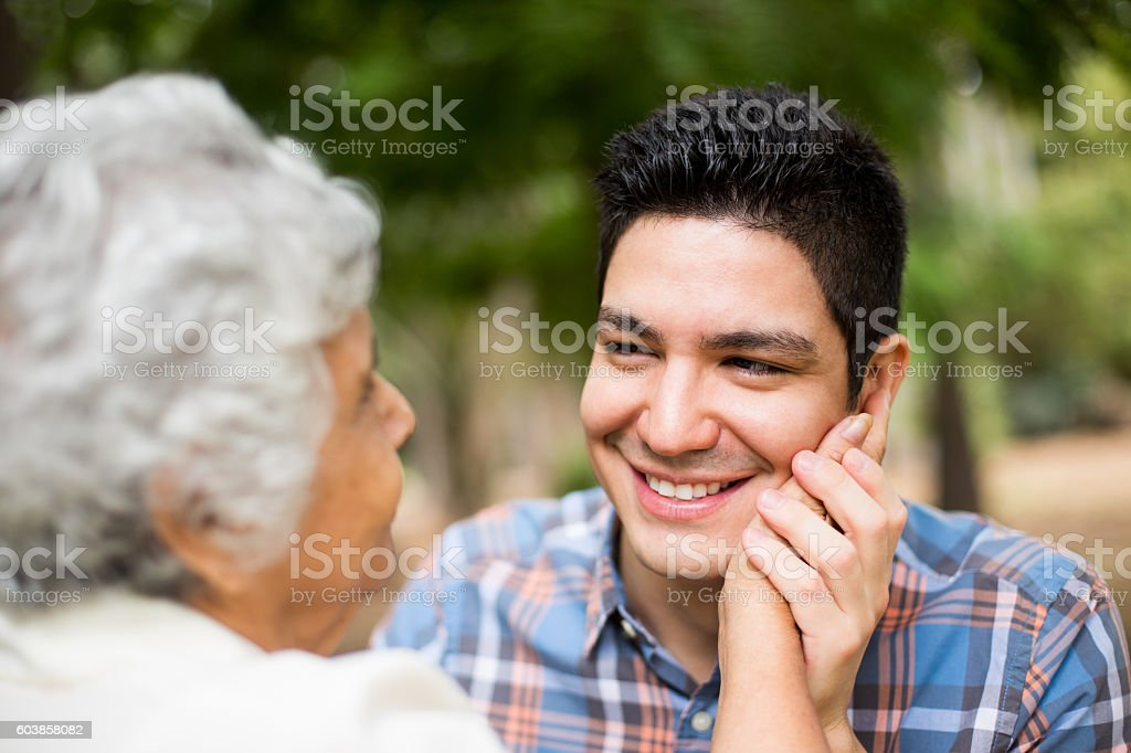 Senior latin woman with hand on cheek of grandson – Foto