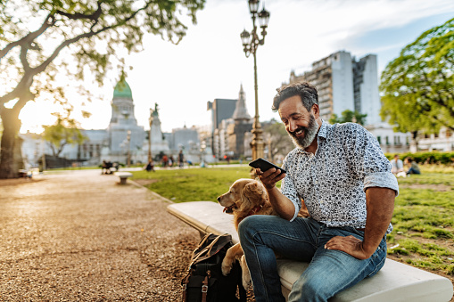 Mature Latino man with beard any stylish casual clothing in springtime day in Buenos Aires, Argentina walking his Retriever dog