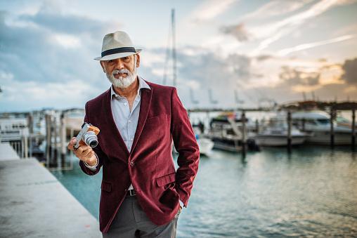Senior Latino tourist traveling to sea side and using camera