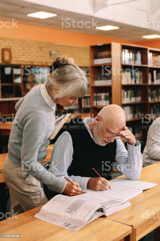 Senior Lecturer Helping An Elderly Man In University Class Stock Photo Download Image Now Istock