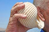Senior listening to a shell