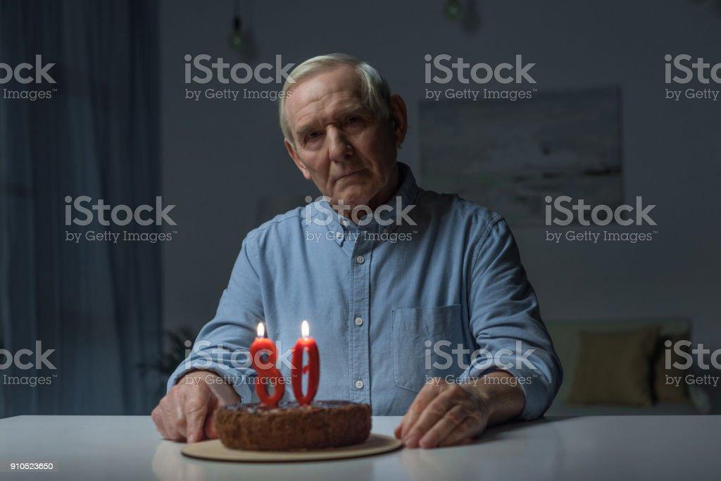 Homem solitário sênior comemorando 80 º aniversário com bolo e queimando velas números - foto de acervo