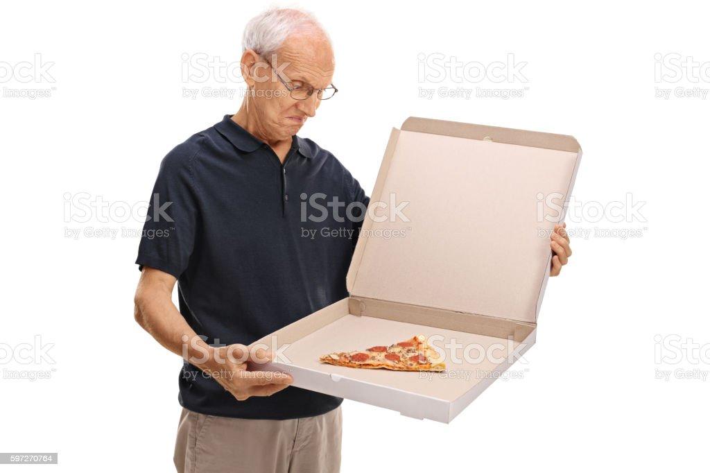 Senior looking at a pizza box photo libre de droits