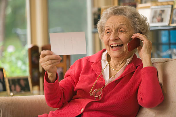 Senior looking at photograph and talking on cell phone stock photo