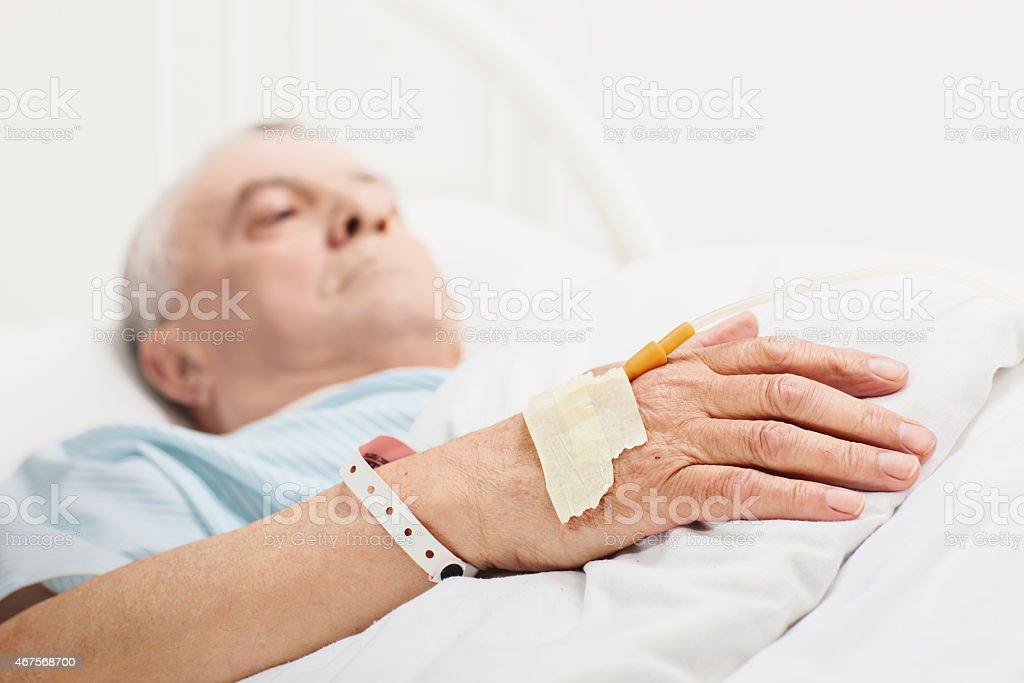 Senior lying in hospital bed with iv set on hand stock photo