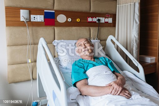 Male patient in hospital gown with arms folded on bedclothes, pensive expression, recovering from treatment