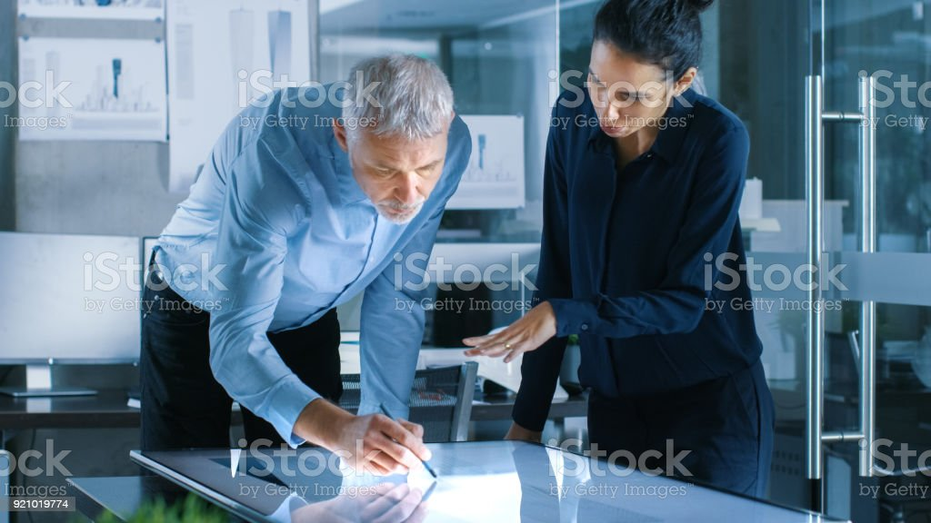 Senior Male and Young Female Architectural Designers Draw Building Concept on a Graphics Tablet Display Vertical Touchscreen Table. They Use Gestures for Zooming Project Model. stock photo