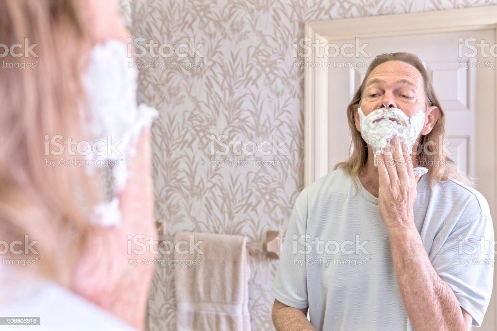 Senior male applies shaving cream to his beard in preparation of shaving off his beard stock photo