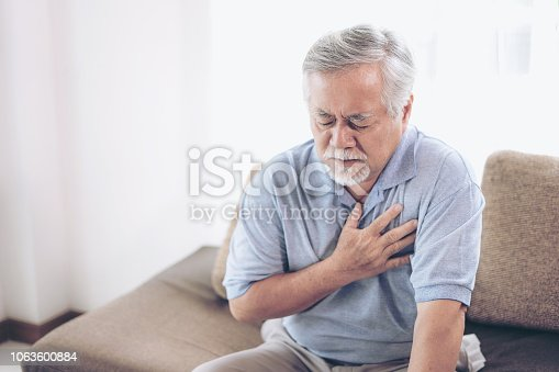 istock Senior male asian suffering from bad pain in his chest heart attack at home - senior heart disease 1063600884