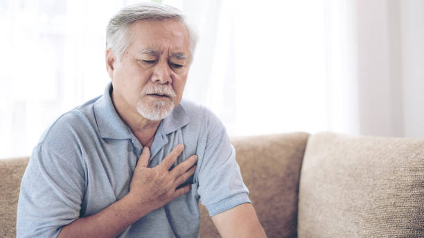 Senior male asian suffering from bad pain in his chest heart attack at home - senior heart disease stock photo