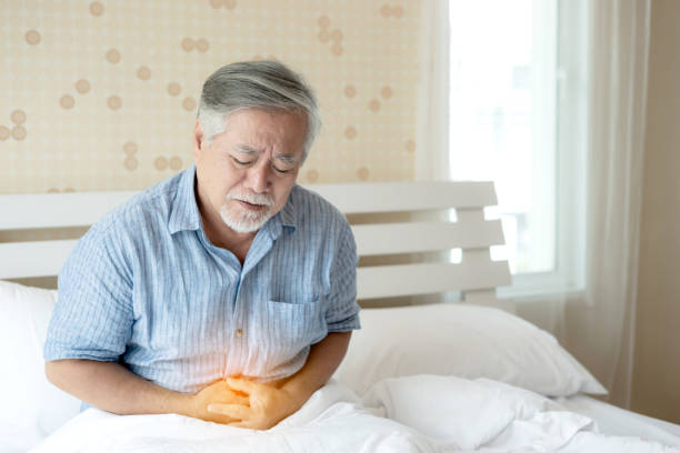 Senior male asian suffering from bad pain in his have a stomachache at home - senior healthcare concept stock photo
