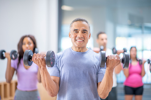 A male senior of Hispanic ethnicity is participating at a group fitness class. He is doing using a dumbbell to exercise.