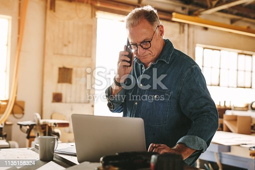 Senior man talking on cell phone and using laptop on work table. Mature carpenter working on laptop and answering phone call in his carpentry workshop.