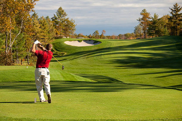 senior male caucasian golfer driving off the tee in fall - golf stock photos and pictures