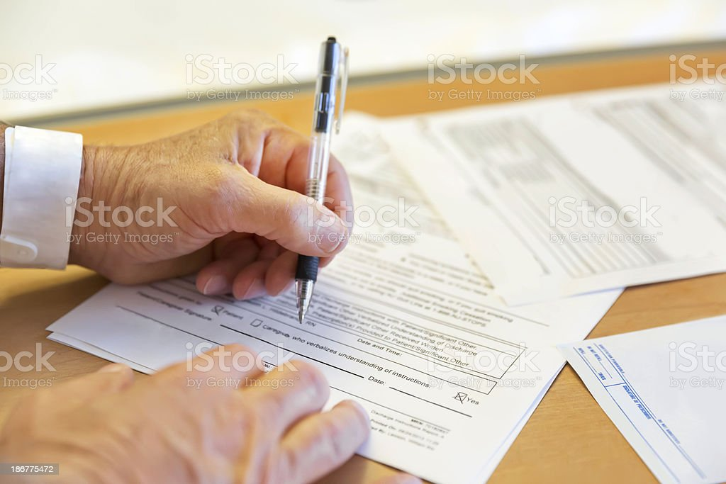 Senior male completes hospital forms - Royalty-free Adult Stock Photo
