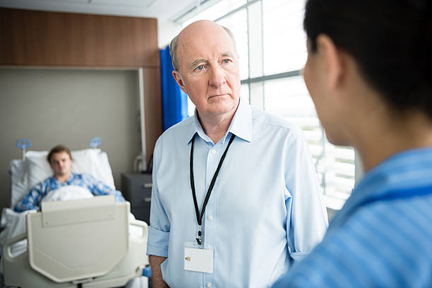 senior male consultant listening to nurse in hospital - australian nurses stock photos and pictures