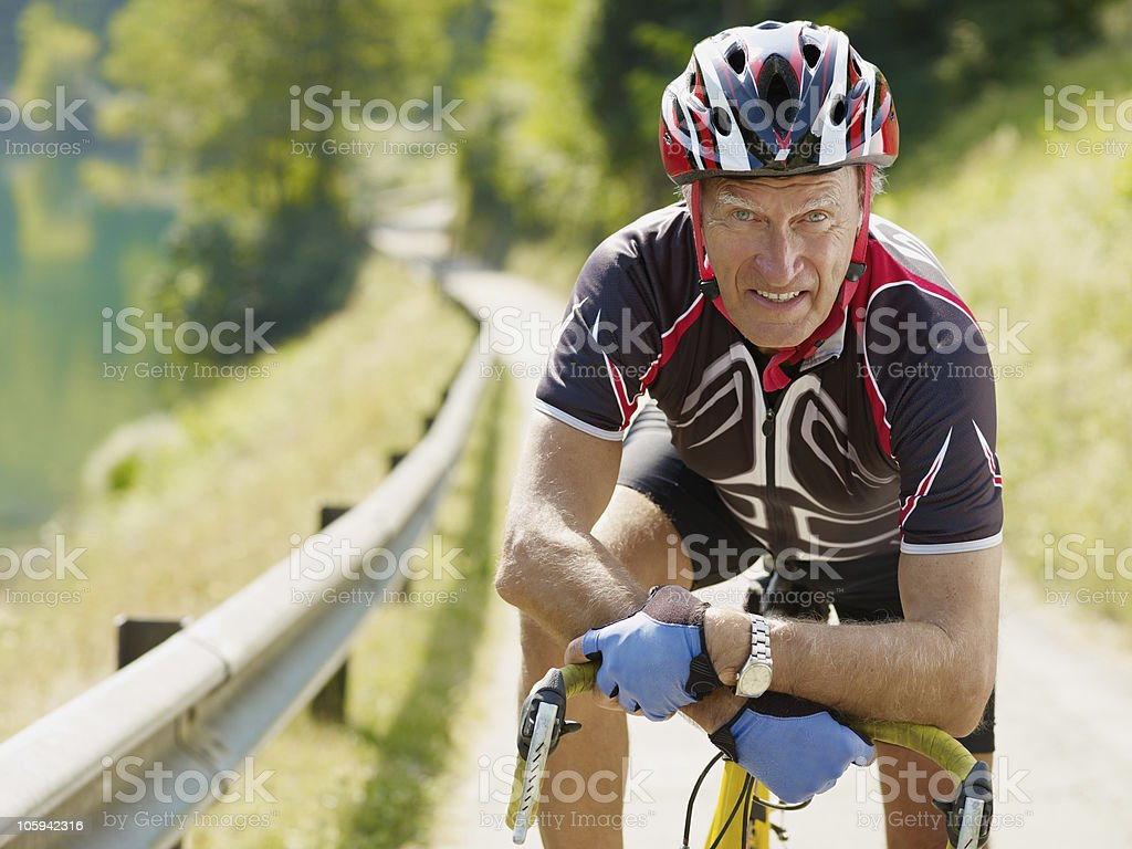Senior male cyclist resting on a country bike path royalty-free stock photo