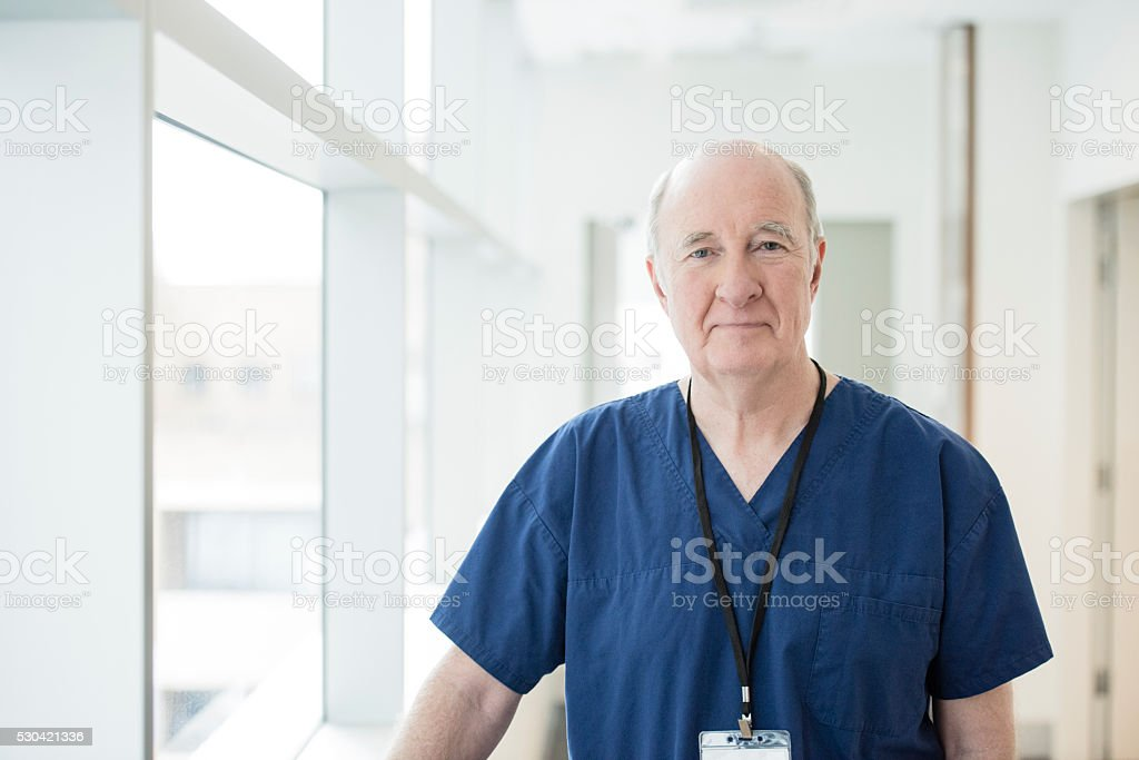 Senior male doctor in blue uniform looking at camera Portrait of senior Caucasian surgeon in modern hospital. Medical professional facing camera wearing blue top and lanyard 60-69 Years Stock Photo