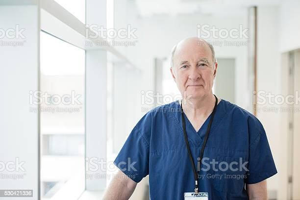 Senior Male Doctor In Blue Uniform Looking At Camera Stock Photo - Download Image Now